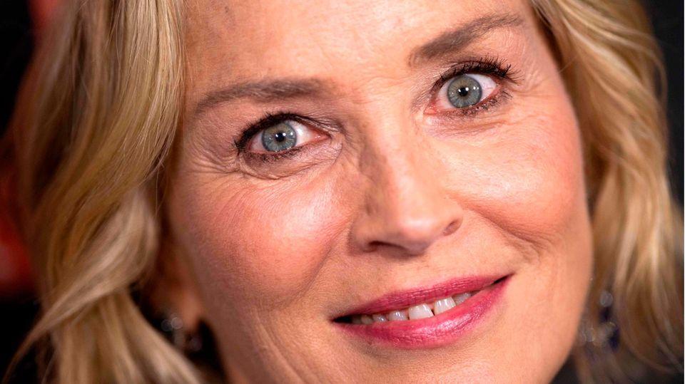 Mit aufgerissenen Augen legt Sharon Stone ihren Kopf schräg und schaut mit leichtem Lächeln in die Kamera