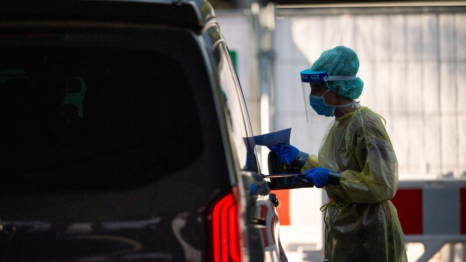 Garmisch-Partenkirchen: Eine Mitarbeiterin gibt in einem Testzentrum einer Familie in einem Auto Infomaterial zum Coronavirus