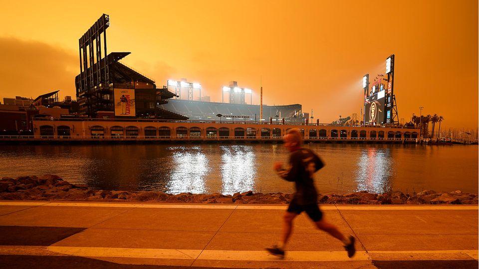 Ein Mann joggt entlang der McCovey Cove vor dem Oracle Park Stadion in San Francisco