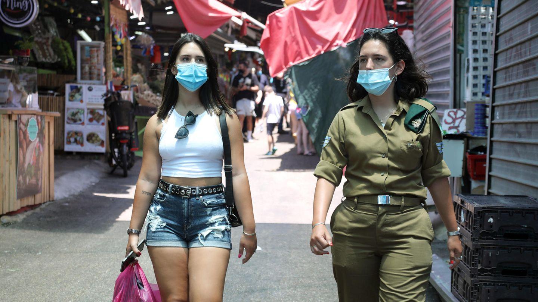 Israelis, die Nasen- und Mundschutz tragen, gehen durch einen Markt