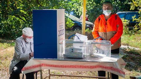 Russland, Tambow: Ein Mann mit Mundschutz füllt hinter einer Trennwand seinen Stimmzettel aus. Mitglieder der Wahlkommission der Bezirke warten im Freien in einem Wahllokal auf die Wähler.