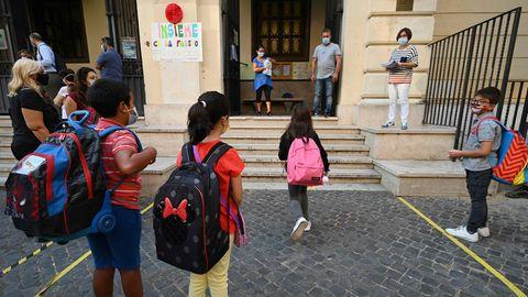 Schüler mit Maske warten vor einer Schule in Rom an einer Abstandsmarkierung