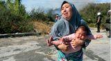 Frau hält ihr Baby auf der Flucht vor einem kleinen Feuer auf einem Feld in der Nähe der Stadt Mytilene