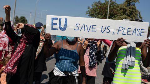 """Migranten protestieren auf Lesbos mit einem Schild """"EU save us, please!"""""""