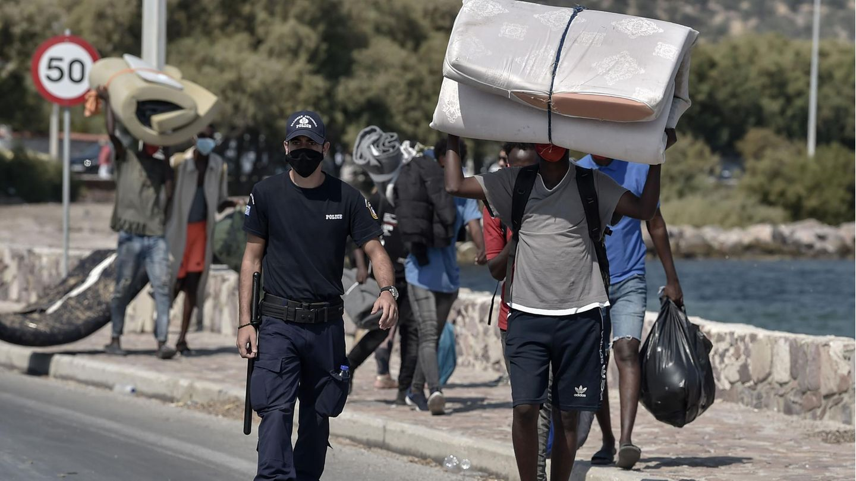 Polizist begleitet Flüchtlinge aus Moria in ein neues Camp