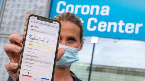 Eine Frau hält ihr Smartphone in die Kamera, mit dem sie sich zuvor am Flughafen München für den Coronatest angemeldet hat