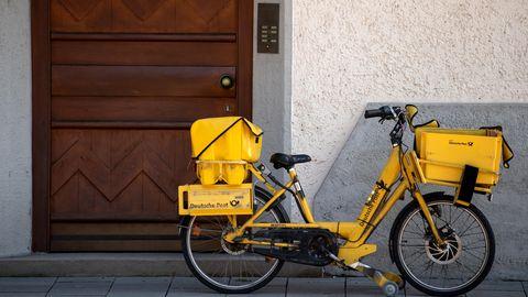 Post-Fahrrad lehnt an einer Hauswand