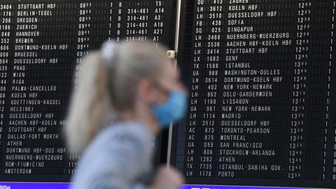 Frau mit Mundschutz steht im Terminal 1 des Frankfurter Flughafens in der Abflughalle vor einer großen Anzeigetafel
