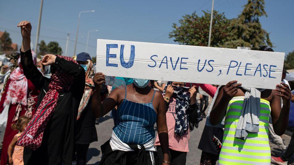 """Griechenland, Lesbos: Migrantinnen und Migranten halten ein Schild mit der Aufschrift """"EU, save us, please"""""""