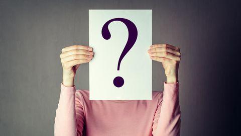 Eine Frau hält sich ein Fragezeichen vor den Kopf
