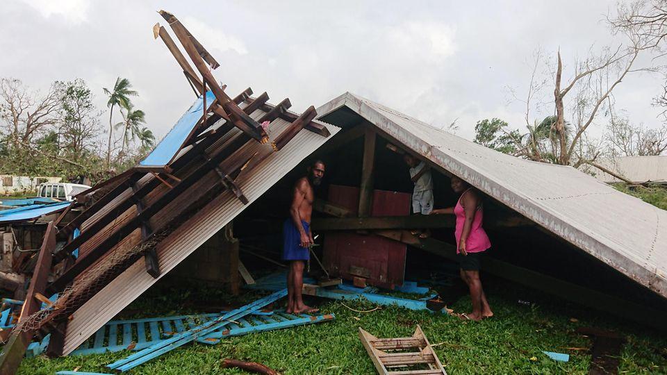 Familie steht auf Vanuatu in den Trümmern ihres durch einen Wirbelsturm zerstörten Hauses