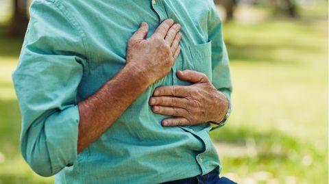 Ein Mann hält sich die Brust