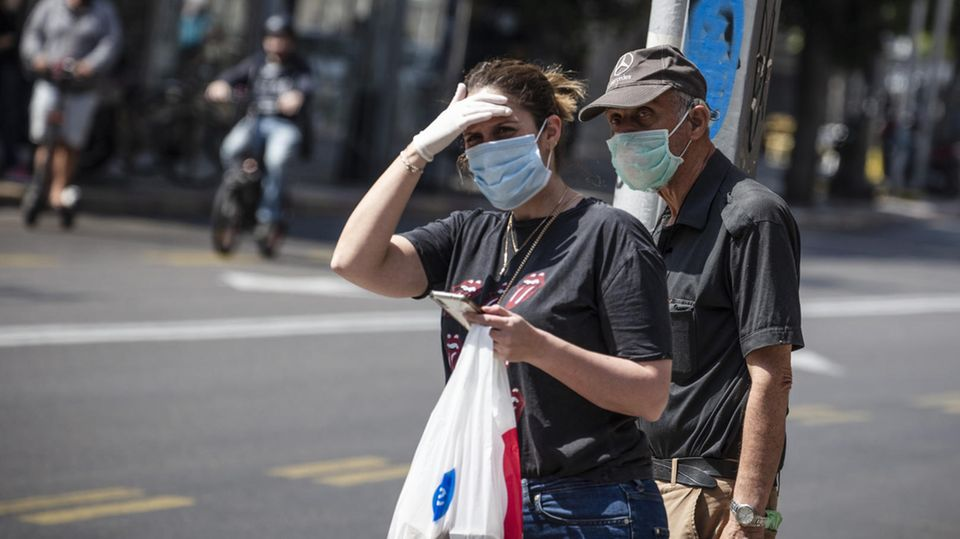 Israel, Tel Aviv: Passanten mit Mundschutz stehen auf der Straße