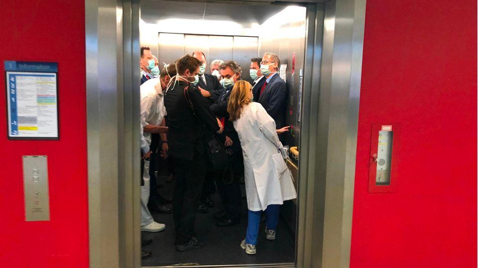 Volker Bouffier, Jens Spahn und andere Personen stehen dicht gedrängt im Aufzug