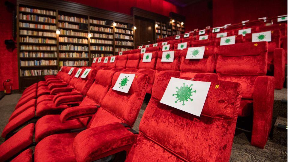 Einzelne Sitzplätze in einem Kinosaal in Hannover sind mit Zetteln mit aufgedrucktem angedeuteten Virus-Symbol abgesperrt