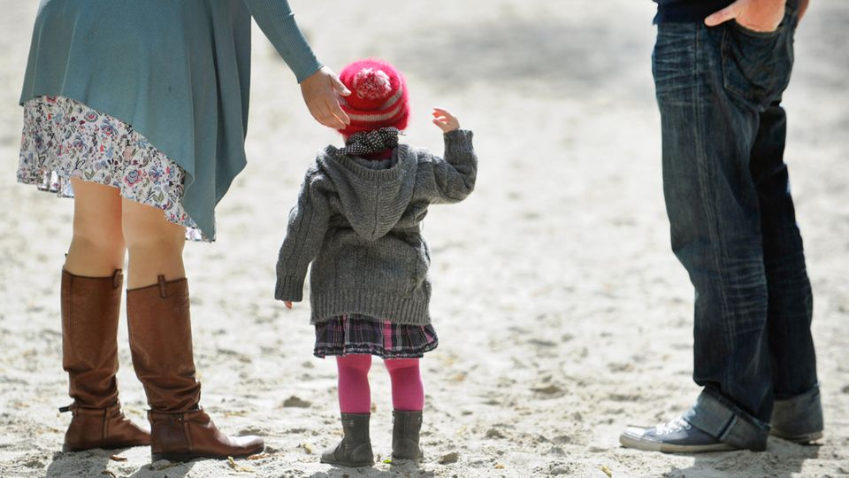 Ein Kind steht auf einem Spielplatz zwischen seinen Eltern