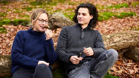 Der Autor und eine Frau sitzen im Wald, sie riecht an einem Pilz