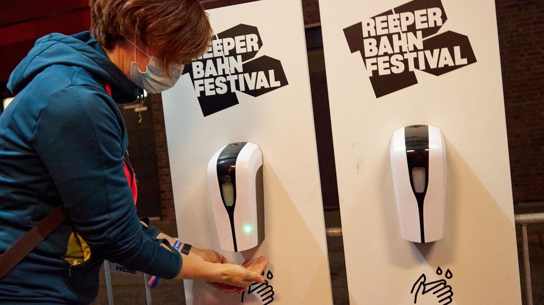 Eine Konzertbesucherin desinfiziert sich an einem Spender ihre Hände vor dem Eingang zum Grünspan in Hamburg