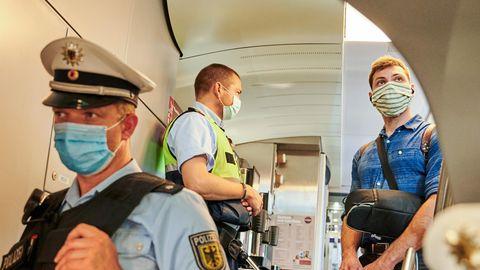 Beamte der Bundespolizei und Mitarbeiter der DB Sicherheit stehen in einem IC