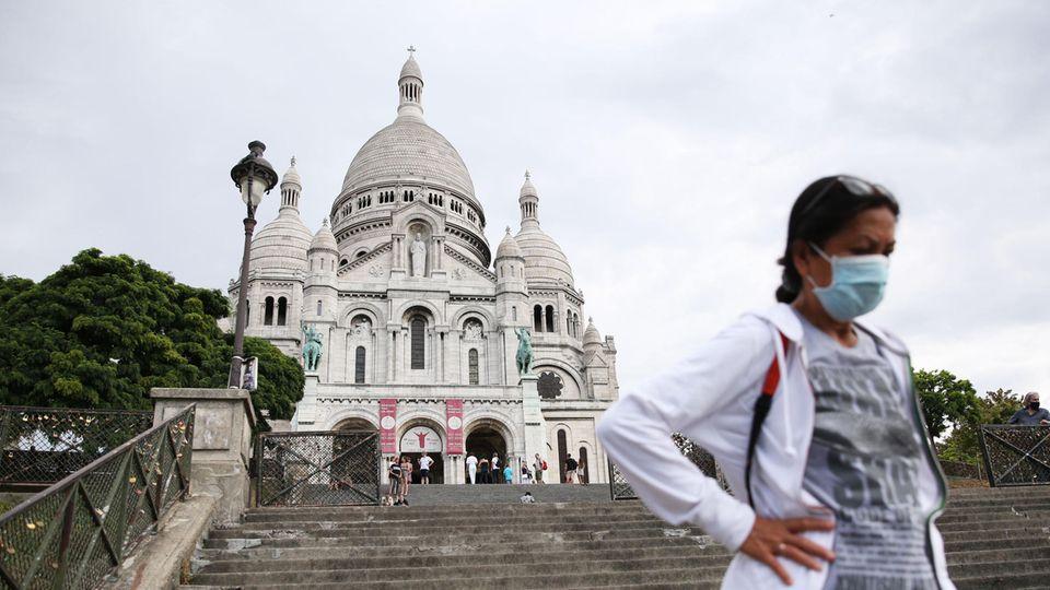 Coronavirus Paris: Eine Frau steht vor der Basilika Sacre-Coeur in Paris