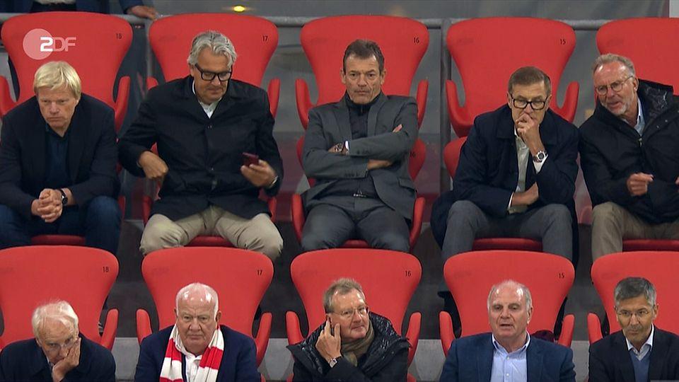 Zehn Funktionäre des FC Bayern sitzen dich beieinander auf der Tribüne