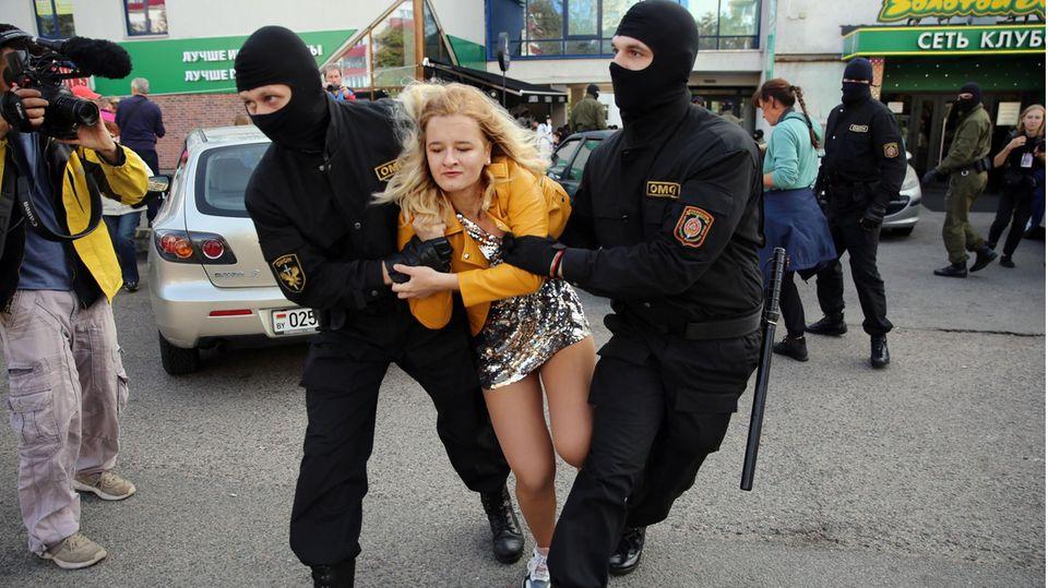 Sicherheitskräfte nehmen eineprotestierende Frau in Minsk fest