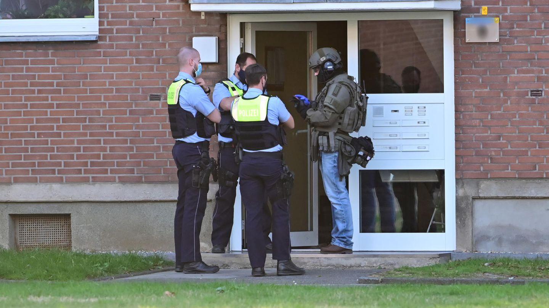 Polizei und ein SEK-Beamter stehen vor der Eingangstür eines Mehrfamilienhauses