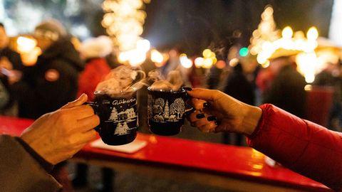 Baden-Württemberg, Breitnau: Zwei Besucherinnen stoßenauf einem Weihnachtsmarkt mit Glühwein an