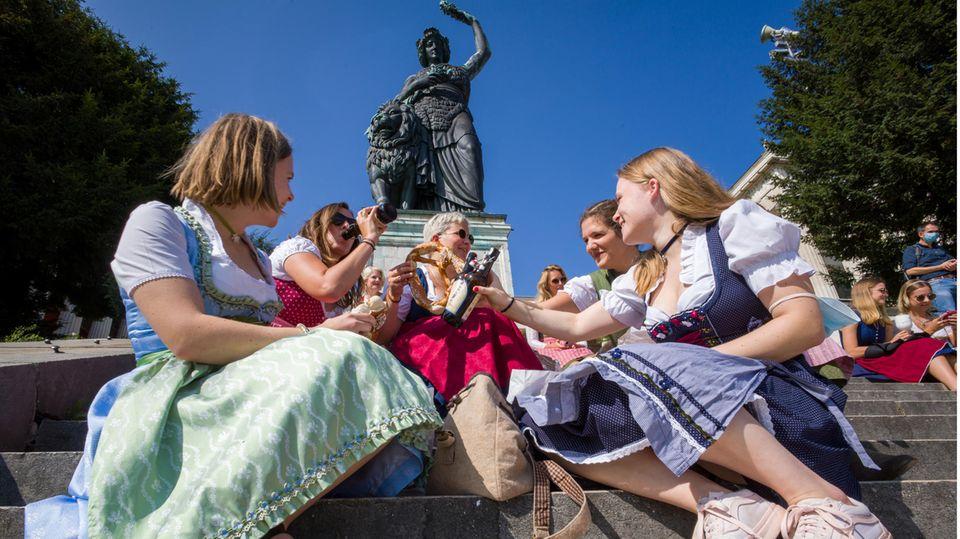 Frauen in Tracht sitzen auf dem Wiesn-Gelände auf der Freitreppe unterhalb der Bavaria-Statue
