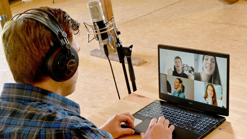 Ein Mann in blauem Karohemd sitzt an einem Laptop, auf dessen Monitor die Gesichter von vier Jugendlichen zu sehen sind