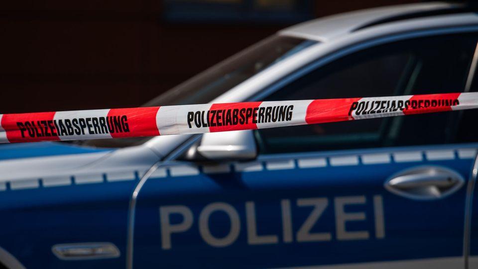 Ein Polizeiauto steht hinter einem Absperrband
