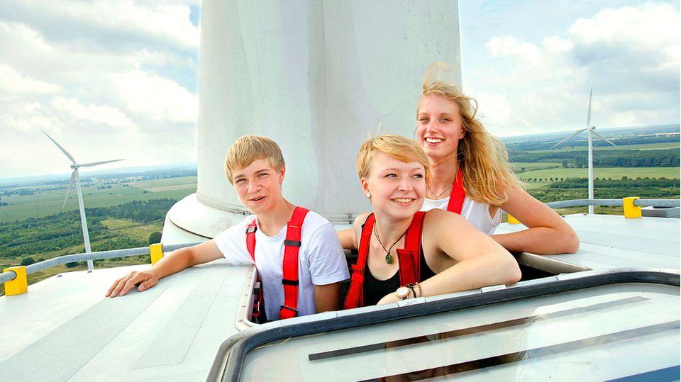 Drei Jugendliche schauen aus einer Windradgondel heraus