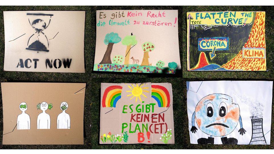 Selbst gemalte Pappschilder zum Thema Klimawandel