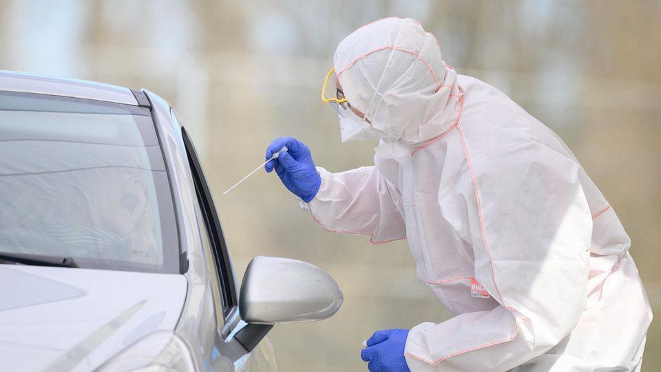 Ein Mitarbeiter führt in einem Corona-Abstrichzentrum einen Test auf das Coronavirus Sars-Cov-2 durch