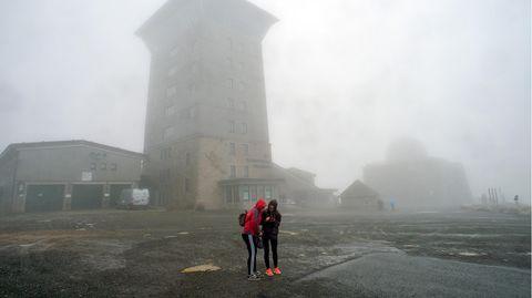 Zwei Touristinnen stehen mitten im Sturm auf dem Brocken vor dem Brokenhotel