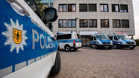 Fahrzeuge der Bundespolizei stehen bei einer Razzia vor einem Bürogebäude in der Region Hannover