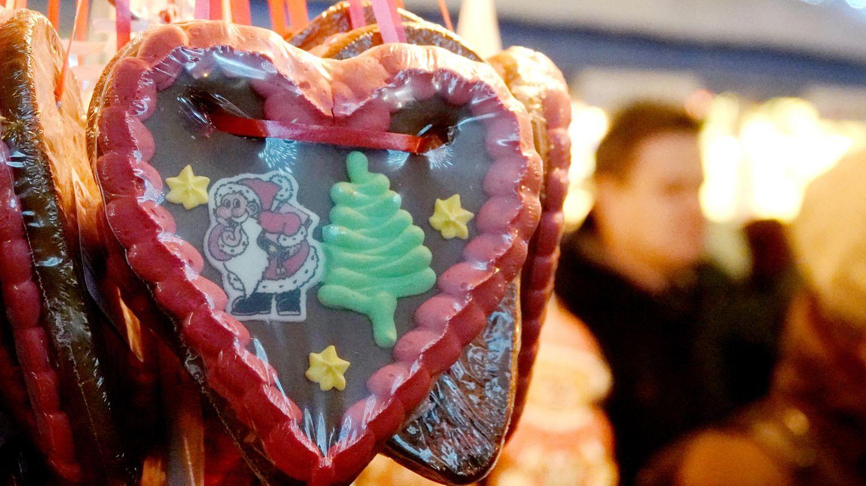 Ein Lebkuchenherz mit einem Tannenbaum und einem Weihnachstmann hängt an einem Stand auf einem Weihnachtsmarkt
