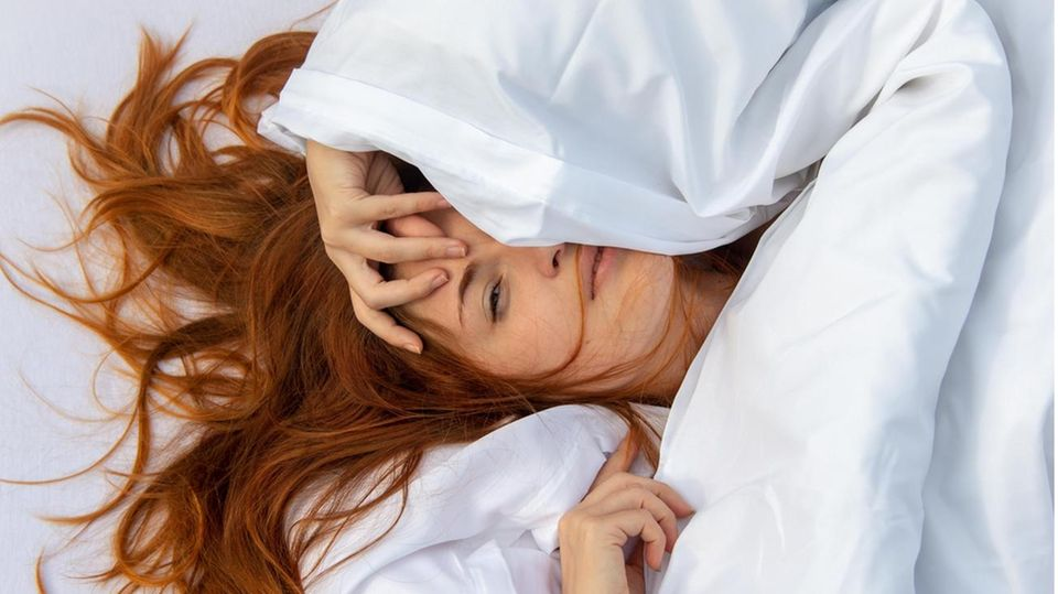 Eine Frau kuschelt sich in ihre Decke