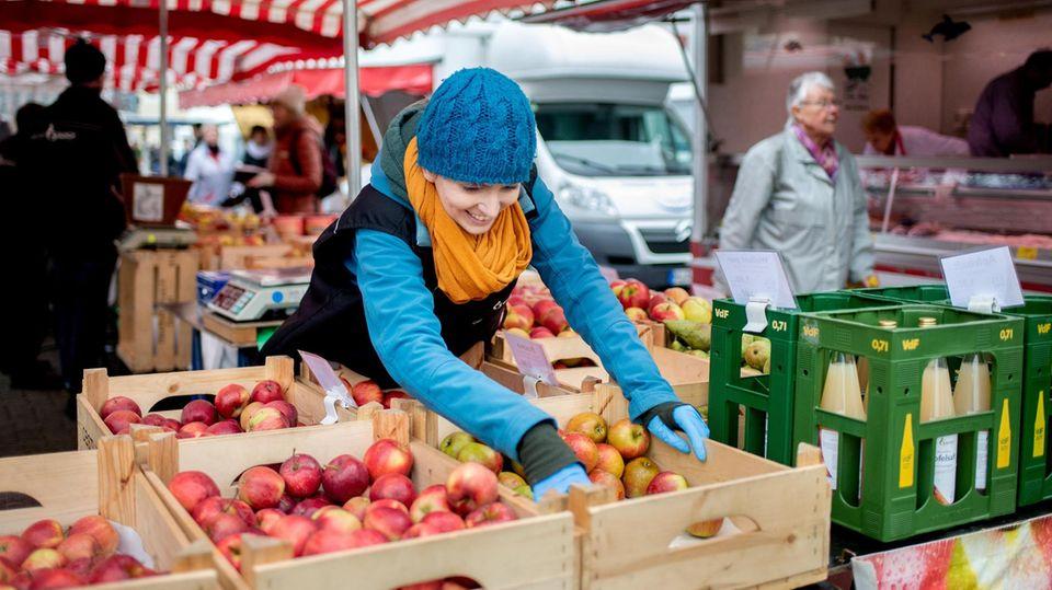 Eine Obsthändlerin auf einem Wochenmarkt