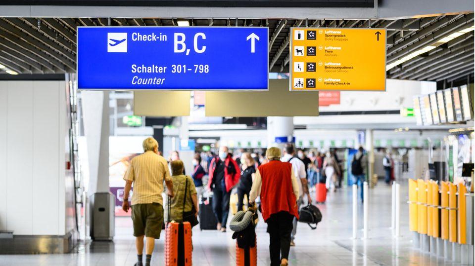Reisende gehen am Flughafen mit Gepäck durch die Abflughalle