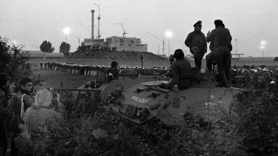 """24. September 1977: """"Sturm auf den Brüter""""  Es war der bis dato größte Polizeieinsatz der Bundesrepublik: Am letzten Septemberwochenende 1977 wurden am Niederrhein rund 8000 Polizisten aus fünf Bundesländern und Beamte des Bundesgrenzschutzes zusammengezogen, um den """"Sturm auf den Brüter"""" zu verhindern. Atomkraftgegner hatten zu Großprotesten gegen den Bau des Kernkraftwerks Kalkar vom TypSchneller Natriumgekühlter Reaktor (""""schneller Brüter"""") zu protestieren – und rund 40.000 Menschen kamen. Nicht immer blieb es gewaltfrei, doch das Gros der Demonstranten verhielt sich friedlich.  Das Kraftwerkwurde letztlich 1985 fertiggestellt, die Betriebsgenehmigung jedoch nie erteilt. So gilt das etwa sieben Milliarden D-Mark (rund 3,5 Milliarden Euro)teure Projekt bis heute als eine der größten Investitionsruinen Deutschlands. Heute dienen das Gelände und die Gebäude als Freizeitpark. Und auch das Zeitalter der Atomenergie in Deutschland neigt sich dem Ende zu."""