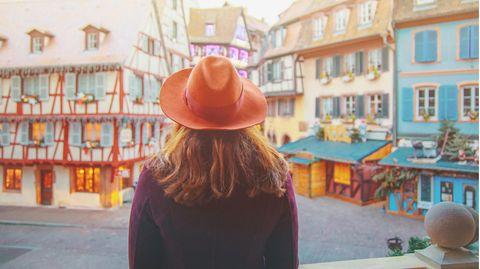 Eine Frau steht in Straßburg mit dem Rücken zur Kamera