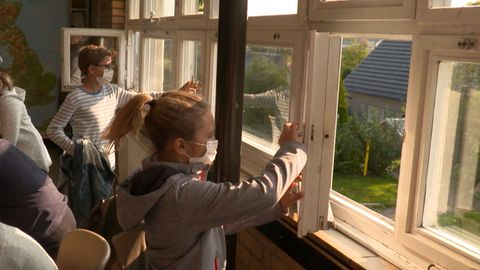 Schüler schließen die Fenster in ihrem Klassenraum.