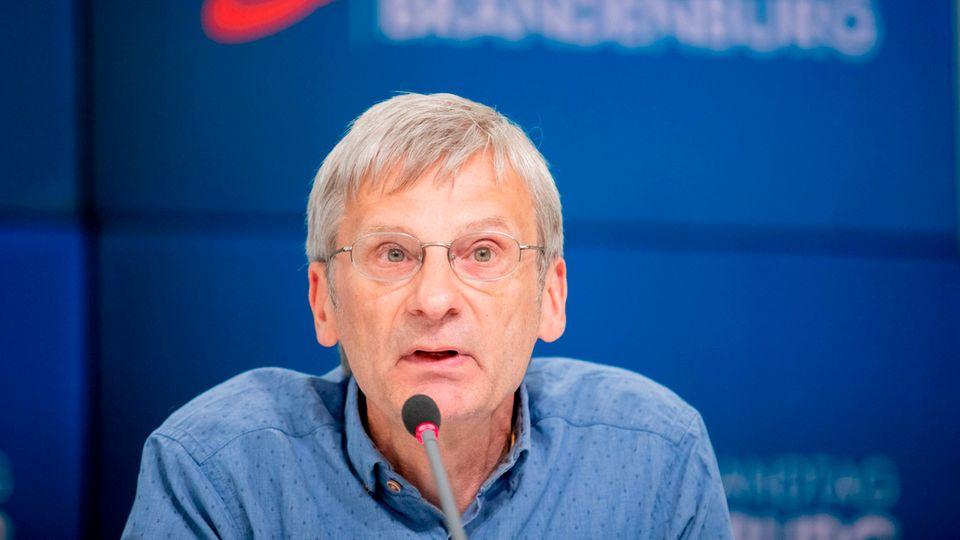 Ein Mann mit grauem Seitenscheitel und randloser Brille sitzt auf einem blauen Podium und spricht in ein Mikrofon