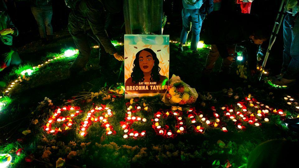 """Auf einem Stück Rasen steht ein gemaltes Porträt einer Afroamerikanerin. Darunter mit Kerzen der Name """"Breonna"""""""