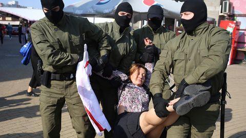 Belarus, Minsk: Polizeibeamte tragen eine Frau am Rande einer Demonstration gegen die Wahlergebnisse in Belarus weg