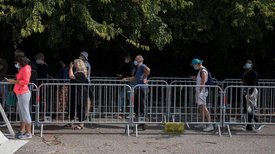 Frankreich, Marseille: Menschen stehen Schlange vor einem mobilen Testzentrum