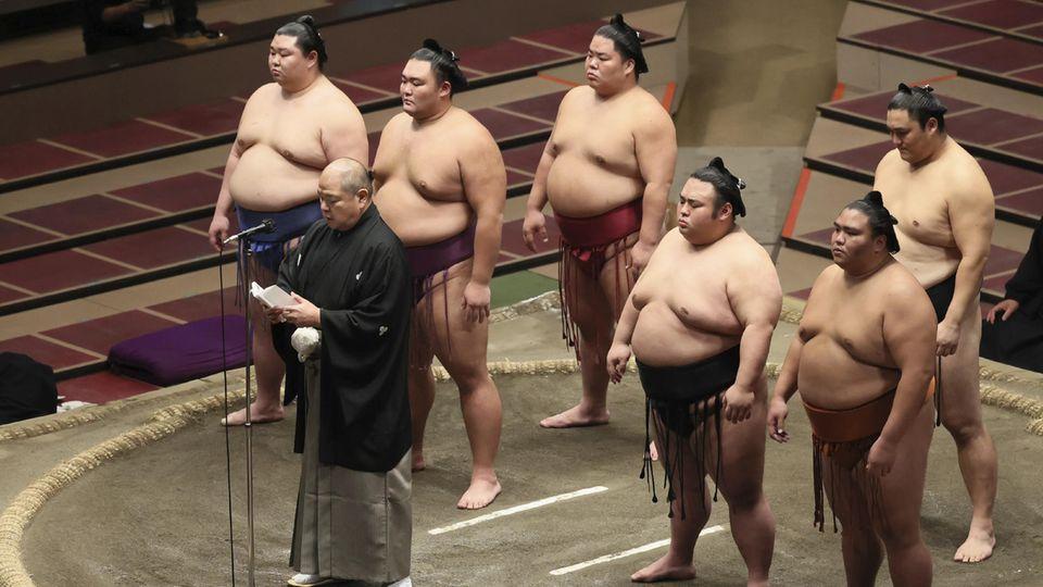 Tokio, Japan:Am letzten Tag des diesjährigen Grand Sumo Tournament hält derVorsitzende der Japan Sumo Association, Hakkaku, eine Rede. In dem nur spärlich gefüllten Stadion dankt er den Menschen für die Zusammenarbeit im Kampfgegen das Coronavirus.