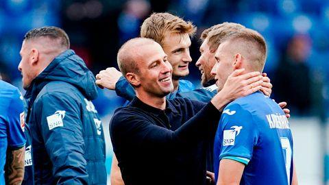 Ein Mann mit kurzrasierten Haaren umarmt einen Fußballer im blauen Trikot mit weißen Aufdrucken