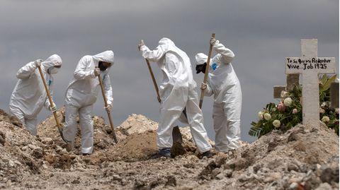 Mexiko, Tijuana: Arbeiter in Schutzanzüge schaufeln Erde bei einer Beerdigung im Rahmen der Covid-19-Pandemie